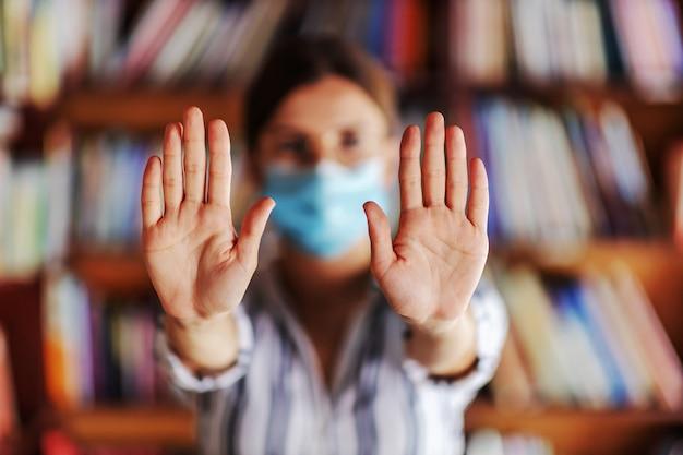 Junges college-mädchen mit gesichtsmaske beim stehen in der bibliothek und beim zeigen sauberer hände. covid pandemiekonzept.
