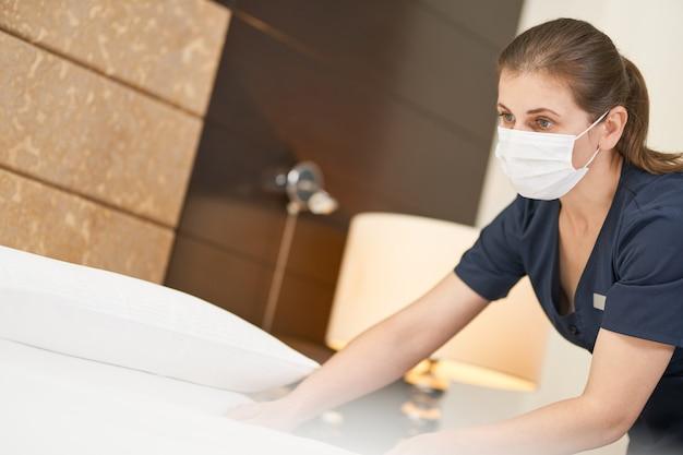 Junges dienstmädchen in maske, das das bett betrachtet und das zimmer säubert. hotelservicekonzept