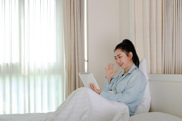 Junges dienstmädchen öffnet vorhänge im hotelzimmer