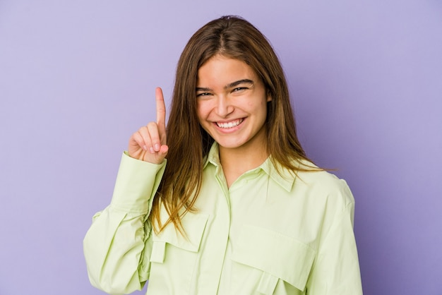 Junges dünnes mädchen teenager auf lila wand zeigt nummer eins mit finger