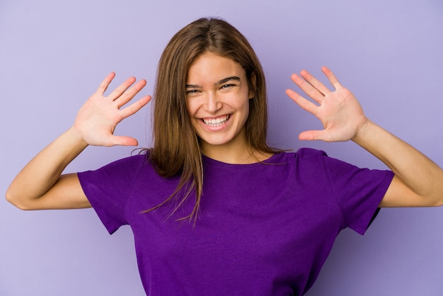 Junges dünnes mädchen teenager auf lila wand zeigt nummer zehn mit händen
