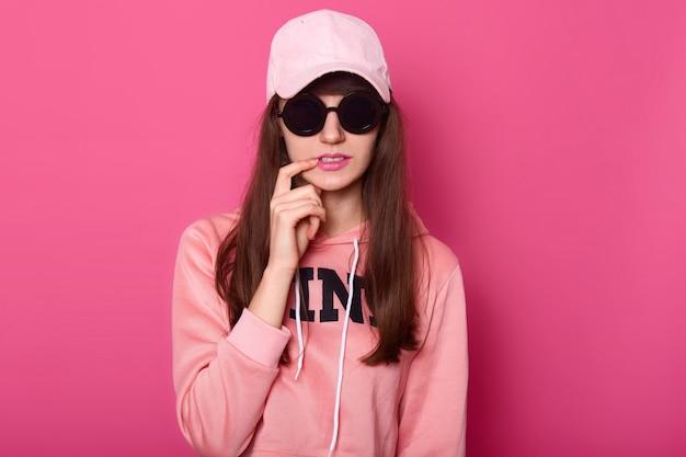Junges dunkelhaariges teenager-mädchen, das stilvollen rosa kapuzenpulli trägt