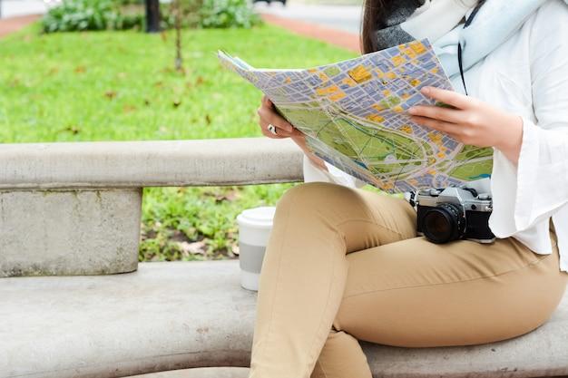 Junges durchdachtes touristisches mädchen in der warmen kleidung mit karte