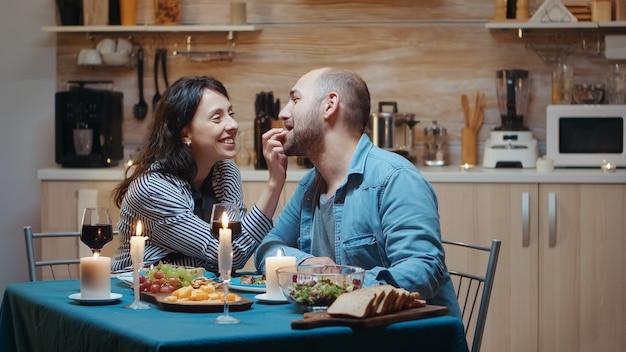 Junges ehepaar mit lustigen momenten beim abendessen. frau und mann beim romantischen abendessen in der küche, gemeinsam zu hause essen, das essen genießen, ihr jubiläum feiern, den urlaub überraschen