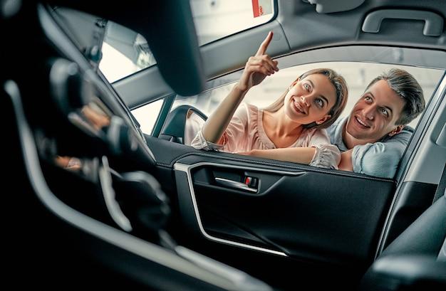 Junges ehepaar schaut in einem autohaus in ein auto. kauf und autovermietung.