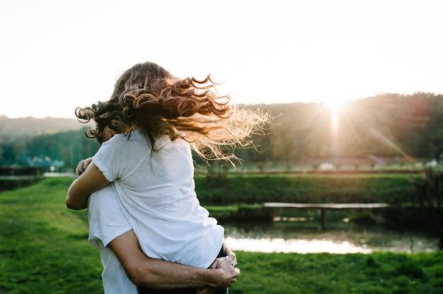 Junges ehepaar umarmt sich, ehemann und ehefrau halten hände an einem nahen see. nahansicht. sommer verliebt.