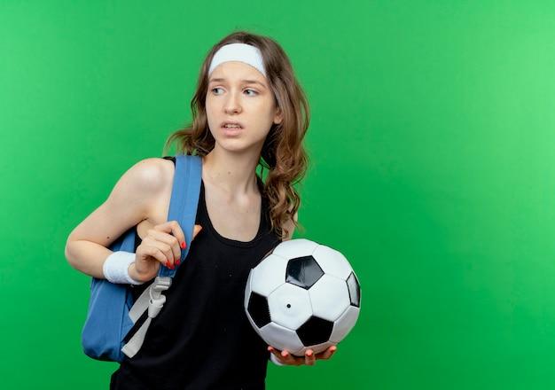 Junges eignungsmädchen in der schwarzen sportbekleidung mit rucksack und stirnband, die fußball suchen, verwirrt beiseite stehend über grüner wand