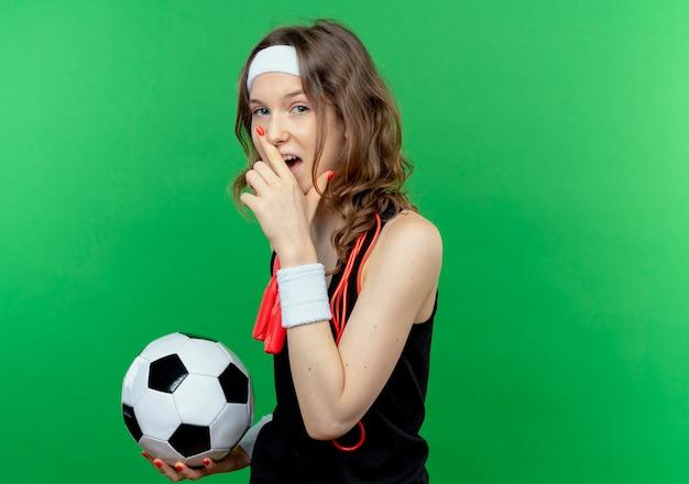 Junges eignungsmädchen in der schwarzen sportbekleidung mit stirnband und springseil um den hals hält fußball, der fröhlich über grüner wand steht