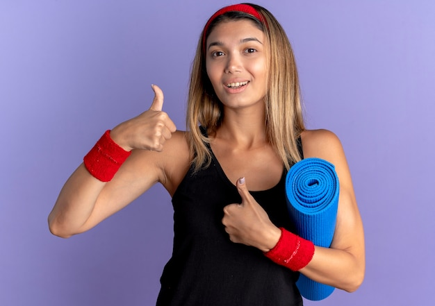 Junges eignungsmädchen in der schwarzen sportbekleidung und im roten stirnband, die yoga-matte betrachten, die kamera lächelnd zeigt daumen hoch stehend über blaue wand
