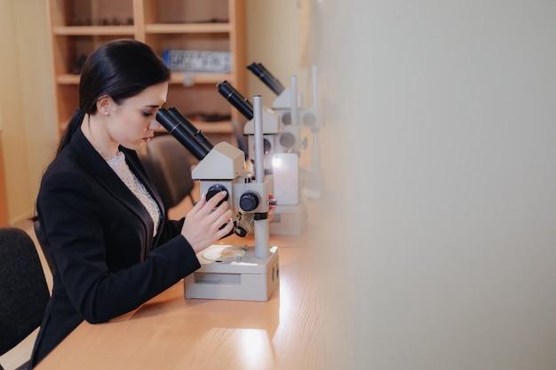 Junges emotionales attraktives mädchen, das am tisch sitzt und mit einem mikroskop arbeitet