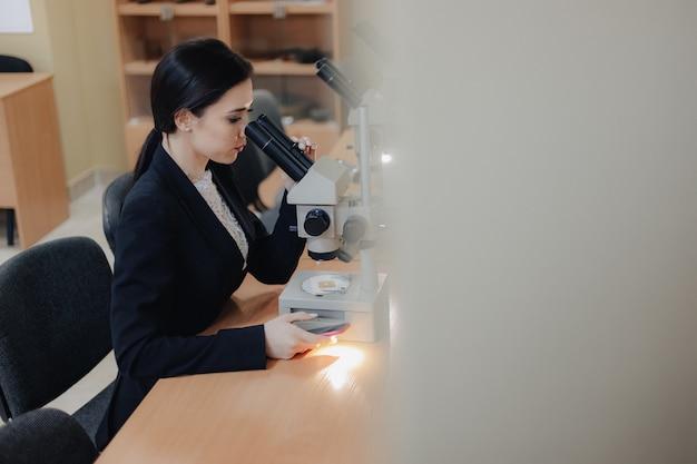 Junges emotionales attraktives mädchen, das am tisch sitzt und mit einem mikroskop in einem modernen büro oder in einem publikum arbeitet