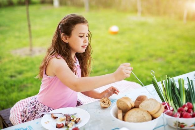 Junges entzückendes mädchen genießt ihr picknickessen, während es am tisch sitzt.