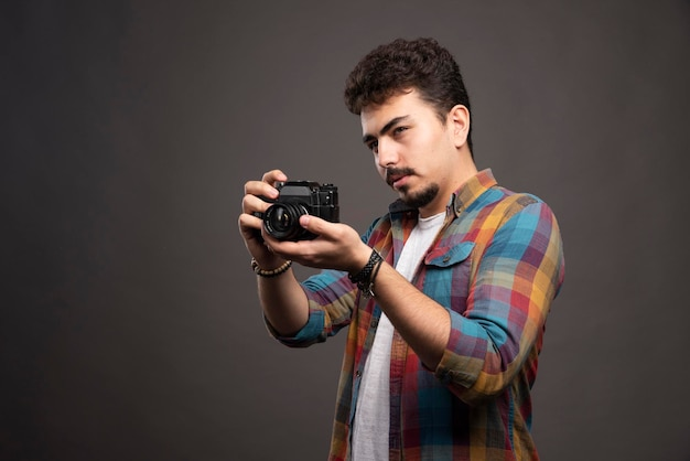 Junges erfahrenes foto, das ernsthafte professionelle fotos macht.