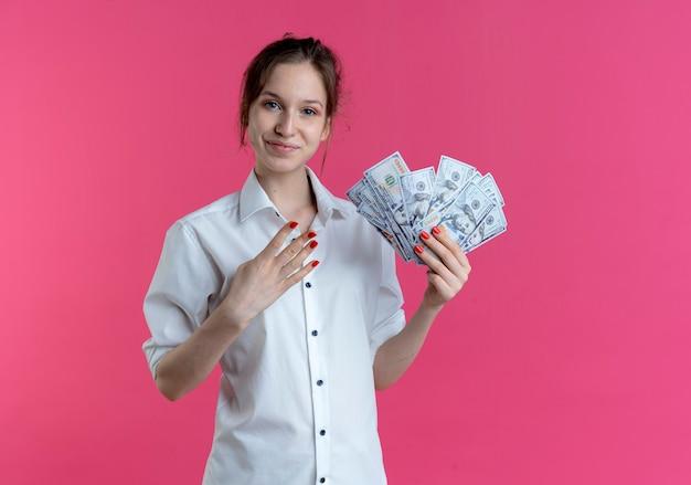 Junges erfreutes blondes russisches mädchen gestikuliert vier, die geld auf rosa mit kopienraum halten