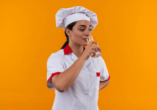 Junges erfreutes kaukasisches kochmädchen in der kochuniform gibt vor, glas wasser zu trinken, das auf orange wand isoliert wird