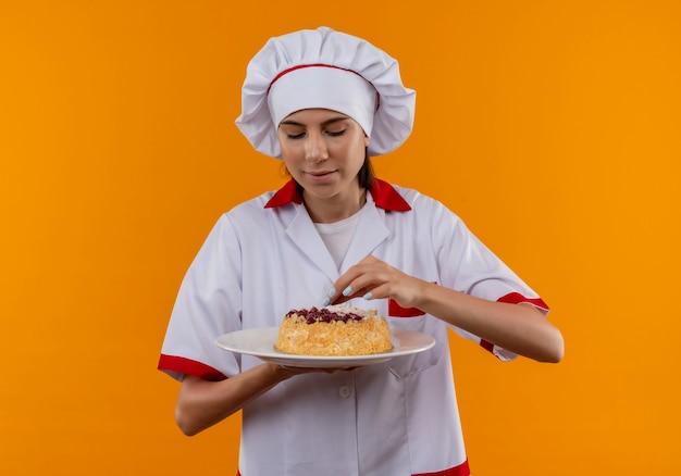 Junges erfreutes kaukasisches kochmädchen in der kochuniform hält und gibt vor, kuchen auf teller zu versuchen, der auf orange raum mit kopienraum isoliert wird