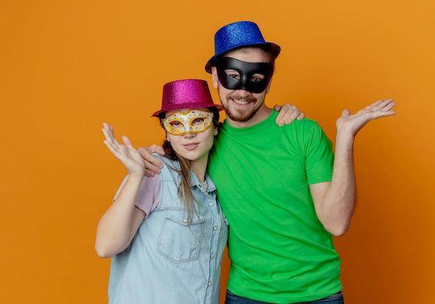 Junges erfreutes paar, das rosa und blaue hüte trägt, setzte auf maskerade-augenmasken auf, die hand suchen, die lokal auf orange wand schaut