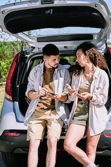 Junges erholsames paar in der freizeitkleidung, die auf autokofferraum sitzt und route ihrer reise bespricht, während sie am sommerwochenende zur wanderung geht