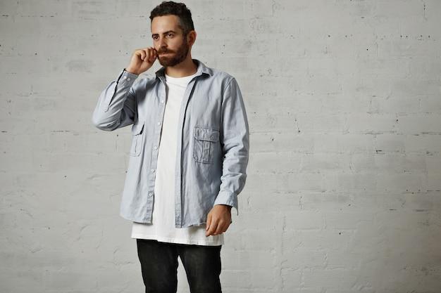 Junges ernstes modell, das ein weißes t-shirt, ein jeanshemd mit knöpfen und schwarze jeans trägt, passt seinen schnurrbart isoliert auf weiß an