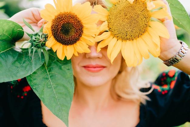 Junges erstaunliches schönes blondes mädchen im schwarzen kleid mit ethnischem musterlebensstilporträt. landmode. nette ungerade glückliche fröhliche frau in der traditionellen slawischen kleidung, die in sonnenblumen im freien aufwirft