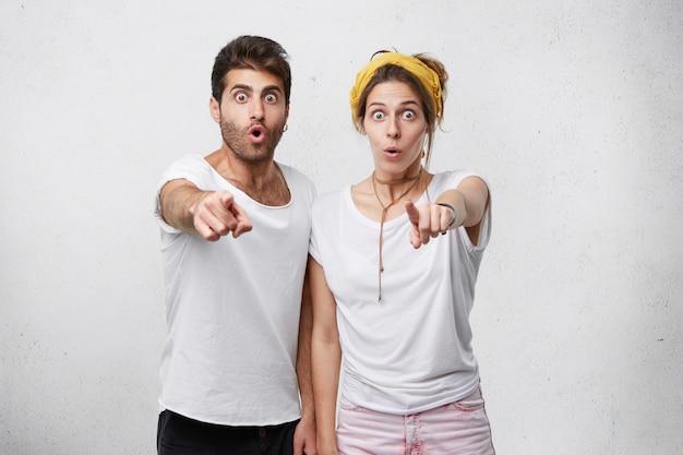 Junges erstauntes paar, das mit zeigefingern auf sie zeigt. mann und frau mit abgehörten augen, die drinnen auf etwas zeigen