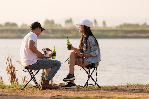 Junges erwachsenes asiatisches paar, das bier neben ihrem zeltcampingplatz während des sonnenuntergangs trinkt.
