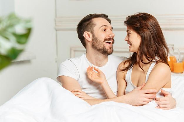 Junges erwachsenes heterosexuelles paar, das auf bett im schlafzimmer liegt