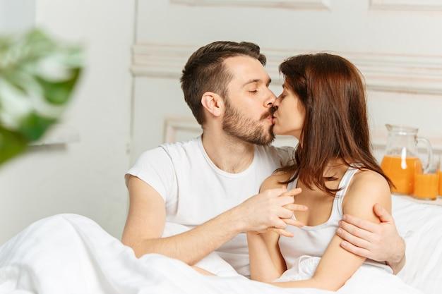 Junges erwachsenes heterosexuelles paar liegt auf dem bett im schlafzimmer