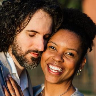 Junges erwachsenes interracial paar an einem strand, kaukasischer mann und afroamerikanerfrau in der freizeitkleidung