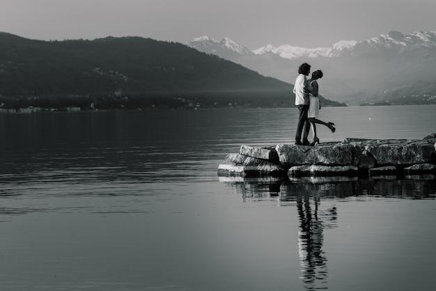 Junges erwachsenes interracial paar auf einem strand, kaukasischer mann und afroamerikanerfrau in der freizeitkleidung, die sommertag am meerufer genießt