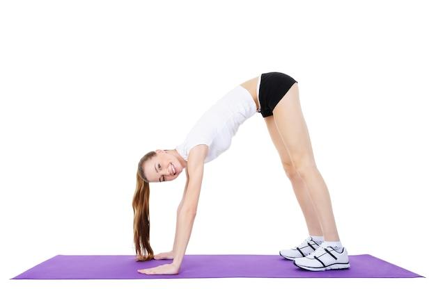 Junges erwachsenes mädchen, das gymnastik tut - lokalisiert auf weiß