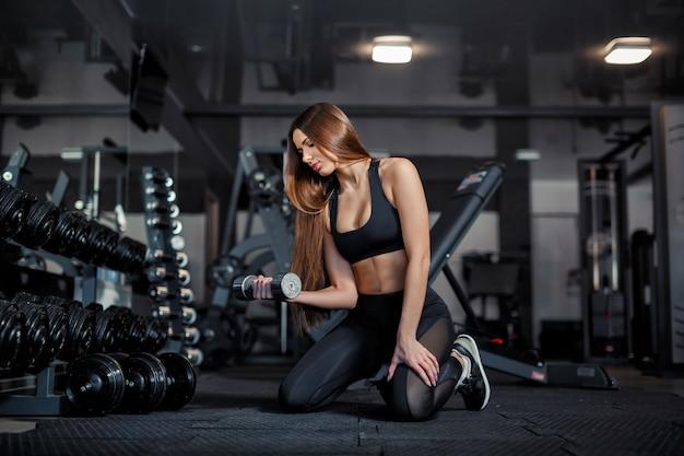 Junges erwachsenes mädchenmodell, das weightlifting in der turnhalle sitzt nahe dem spiegel tut