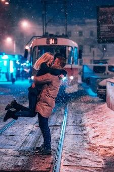 Junges erwachsenes paar auf der schneebedeckten straßenbahnlinie