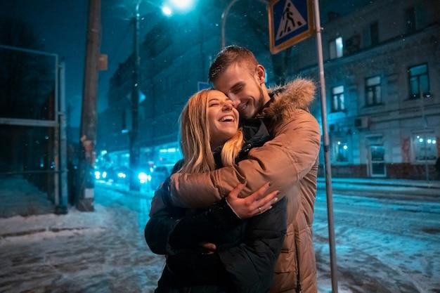 Junges erwachsenes paar, das auf schneebedecktem bürgersteig geht