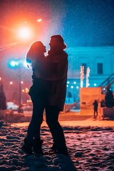 Junges erwachsenes paar in den armen des anderen auf schneebedeckter straße