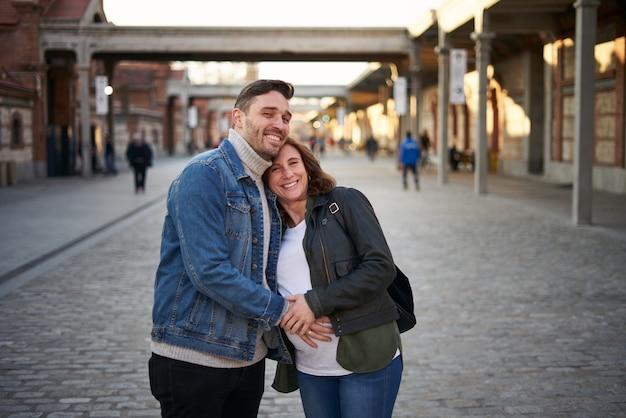 Junges erwachsenes paar wirft glückliche, schwangere frau auf