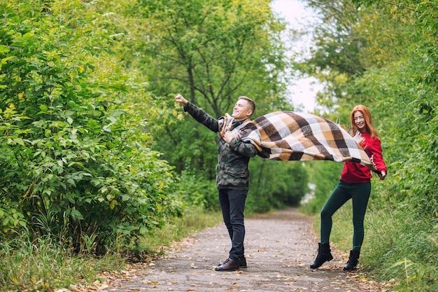 Junges erwachsenes schönes paar in der liebe, die zusammen in der natur im park geht