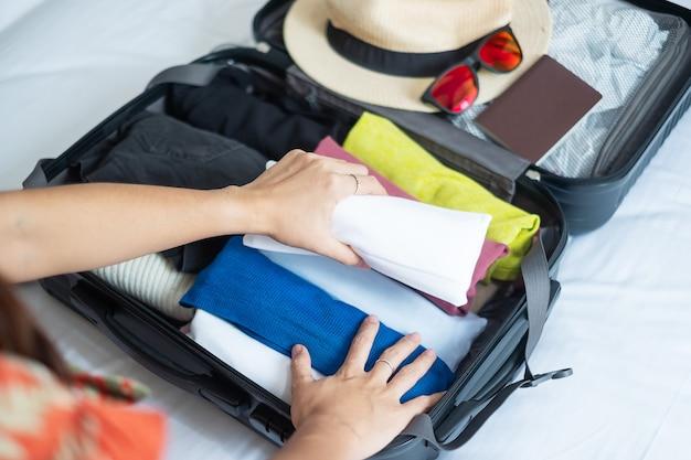 Junges erwachsenes weibliches packgepäck für sommerferien. frau tourist checkliste reiseaccessoires im koffer auf dem bett. zeit zu reisen, entspannung, reise, reise und wochenendkonzepte