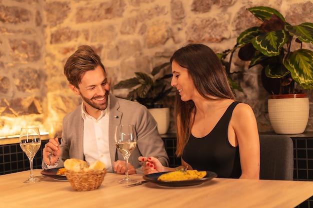 Junges europäisches paar, das abendessen in einem schönen restaurant, das valentinstag feiert