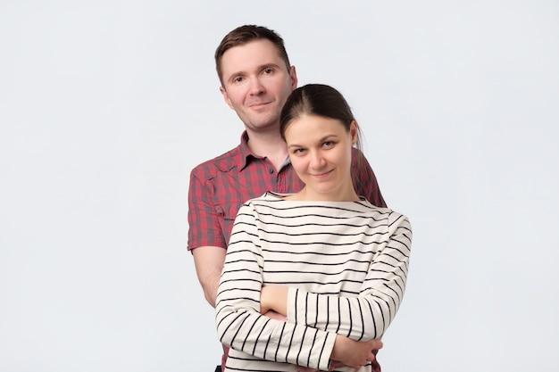 Junges europäisches paar, das gegen weiße graue wand steht
