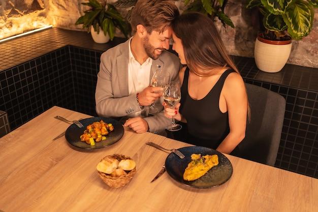 Junges europäisches paar verliebt in ein restaurant, das spaß hat, zusammen zu abend zu essen