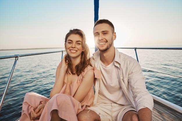 Junges europäisches romantisches paar, das lächelt, während es am bug des bootes sitzt, umarmt und ihre ferien genießt. zwei enge freunde sind vor kurzem etwas mehr miteinander geworden