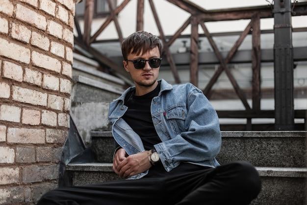 Junges europäisches stilvolles mannmodell in modischer jugendkleidung in der trendigen schwarzen sonnenbrille entspannt sich in der stadt nahe einer mauer. attraktiver kerl hipster, der auf einer hölzernen treppe in der straße ruht.