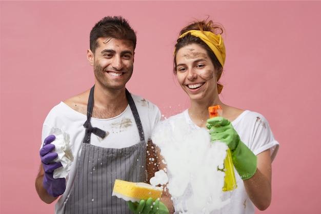 Junges familienpaar, das glasoberfläche mit waschmittel wäscht, das schaum auswischt und sich über gute reinigungsergebnisse freut, die mit waschspray zufrieden sind. schmutzige männliche und weibliche arbeiter, die fenster zu hause putzen