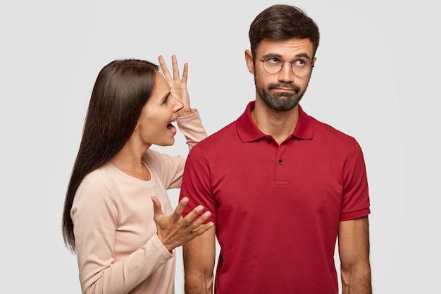 Junges familienpaar hat konflikt. wütende brünette junge europäische frau gestikuliert mit den händen