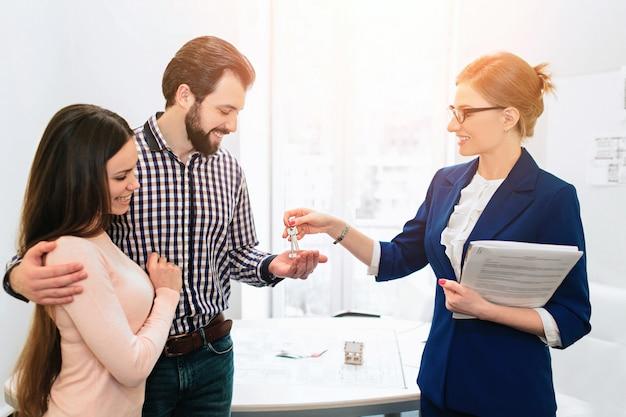 Junges familienpaar kauft mietimmobilien. agent, der mann und frau berät. unterzeichnungsvertrag für den kauf eines hauses oder einer wohnung oder einer wohnung. schlüssel für einige kunden.