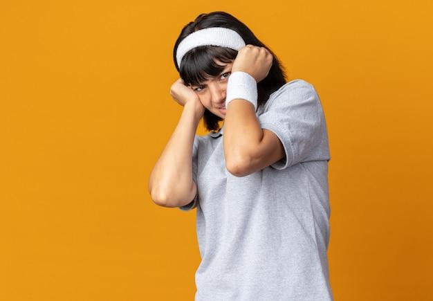 Junges fitness-mädchen, das mit blick in die kamera verängstigt ist und eine verteidigungsgeste mit einem über orange stehenden haarband macht