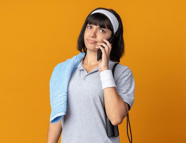 Junges fitness-mädchen, das stirnband mit handtuch auf der schulter trägt und eine wasserflasche hält, die unzufrieden aussieht, während sie auf dem handy über orange spricht?