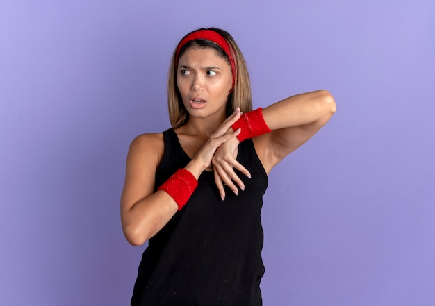Junges fitness-mädchen in der schwarzen sportbekleidung und im roten stirnband, die verwirrt suchen, das ihr handgelenk berührend fühlen, das unbehagen über der blauen wand steht