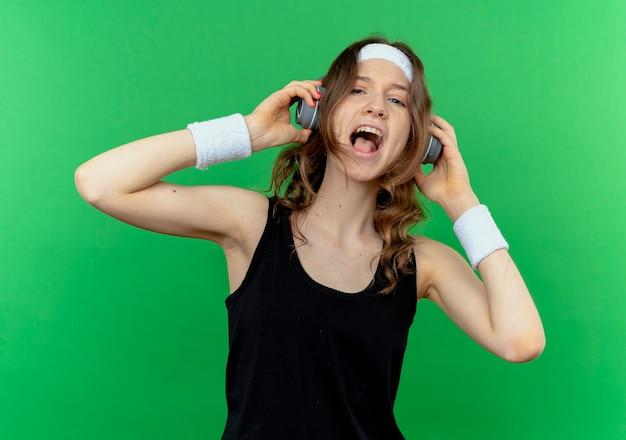 Junges fitness-mädchen in schwarzer sportbekleidung mit stirnband und kopfhörern verrückt glücklich, ihre lieblingsmusik über grün zu genießen